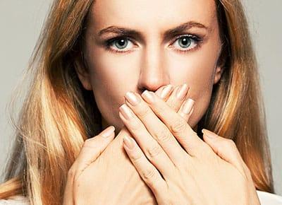 Schöne Frau mit Händen vorm Mund